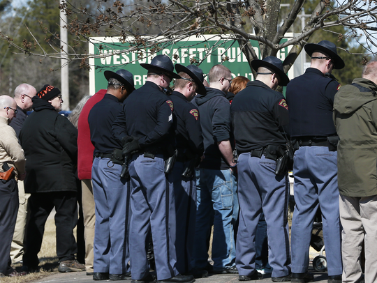 Law enforcement and attendees bow their heads during