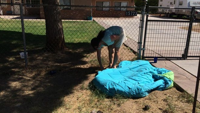 Valerie Collins looks under a blanket where her two dogs lie in Gilbert, Ariz.