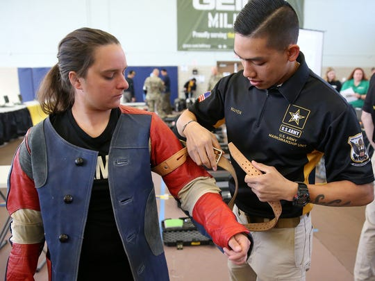 Spc. Brooke Conley, left, of Schofield Barracks, Hawaii, is helped by Staff Sgt. Kevin Nguyen of the U.S. Army Marksmanship Unit prior to air rifle trials Wednesday at Fort Bliss.