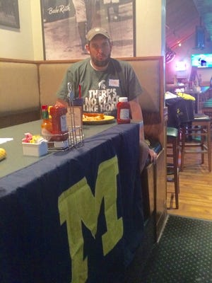 Sports columnist Shad Powers, a Michigan State grad, sits at a booth adorned with a University of Michigan flag Saturday as he visited the U-M spirit group of the Coachella Valley.