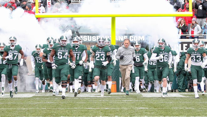 Michigan State football coach Mark Dantonio leads his team onto the field Nov. 19, 2016.