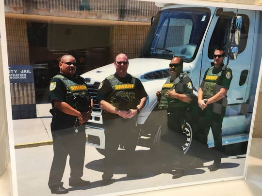 A picture of Corrections Deputy Garry Chambliss with some co-workers in the transportation unit sits on a table in the lobby at the Indian River County Jail on Saturday, Feb. 17, 2017. Chambliss died after he was shot Friday night outside a cousin's home in Gifford.