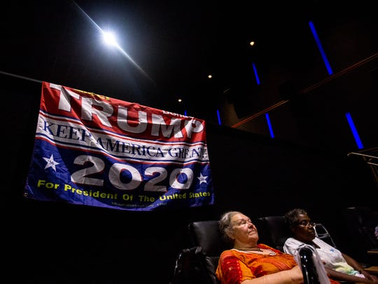 "DeLores Callahan and Toni Rone, both of Phoenix, wait for the film to begin on July 16, 2018, during a showing of the Arizona Republic's Pulitzer Prize-winning project ""The Wall"" at Harkins Theater in Scottsdale, Arizona. Proponents of the US-Mexico border hung a pro-Trump banner in the theater."