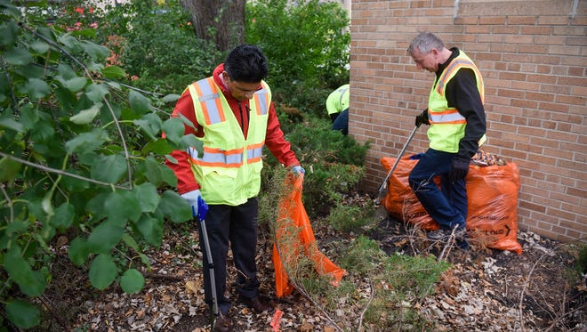 St. Cloud State University Interim President Ashish Vaidya and St. Cloud Mayor Dave Kleis pick up trash along Fifth Avenue Thursday, Oct. 12, in St. Cloud.