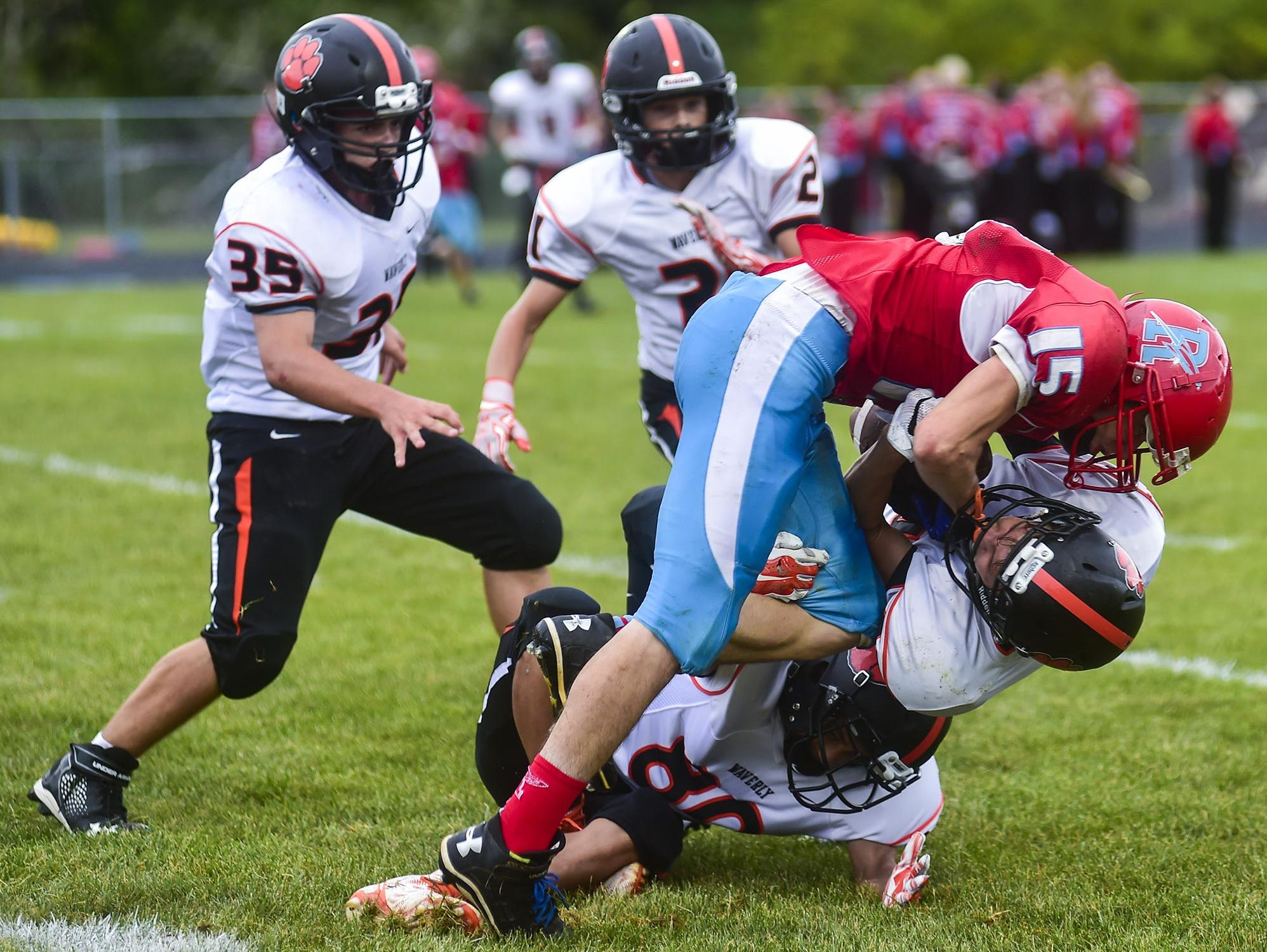 Ridgedale's Alex Brown is taken down by Waverly players as he attempts to drive the ball downfield during the Ridgedale vs. Waverly football game on Saturday.