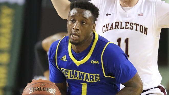Delaware guard Kory Holden pushes the ball up court in front of Charleston's Evan Bailey in the second half during an opening round game of the 2016 CAA tournament in Baltimore.