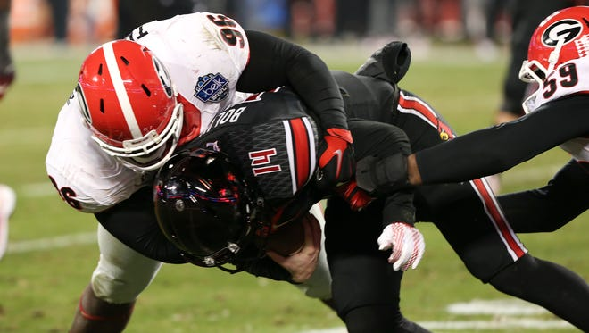 U of L QB Kyle Bolin, #14, was sacked by UGA's Mike Thornton, #96, as UGA's Jordan Jenkins, #59, assisted during the Belk Bowl in Charlotte, N.C.