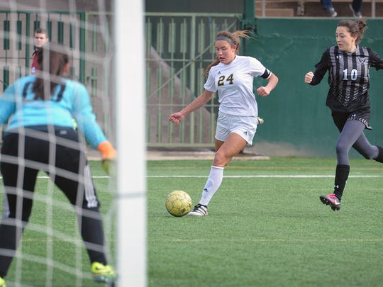 Rider forward Keeley Ayala (24) takes a shot as Canyon Randall keeper Kylee Wright (00) and Nicole Collins (10) defend Thursday afternoon at Memorial Stadium.