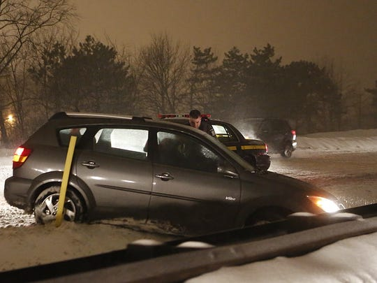 A state trooper helps a driver whose vehicle spun out on the Taconic State Parkway on Tuesday night.