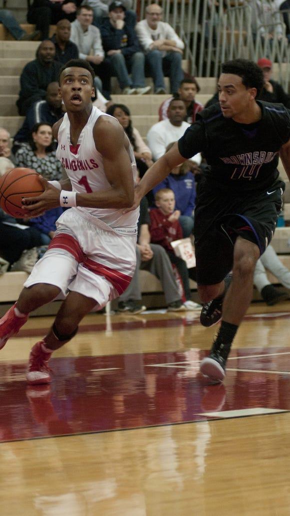 Southport sophomore Paul Scruggs drives for the basket against Brownsburg junior Tyler Kirtz, Nov. 29, 2014.
