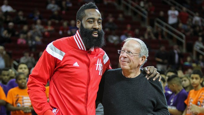Nov 24, 2014; Houston, TX, USA; Houston Rockets owner Leslie Alexander (right) gives a medal to guard James Harden (13) before a game against the New York Knicks at Toyota Center. Mandatory Credit: Troy Taormina-USA TODAY Sports