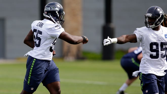 Frank Clark, left, and Marke' Powell exchange a fist bump while taking part in drills at Seattle Seahawks NFL football rookie minicamp Sunday, May 10, 2015, in Renton, Wash.