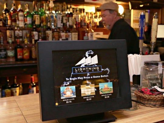 A bartender walks past a now unused raffle machine