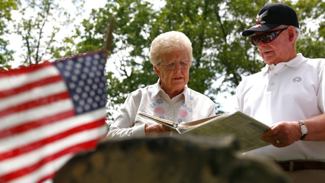 Norma Kahl, with her husband Hal, looks over the history of the Wolford Cemetery in front her great ancestor's gravestone on Friday afternoon. The ancestor is Samuel Osbun, a veteran of the Revolutionary War who was one of the first settlers in Richland County.