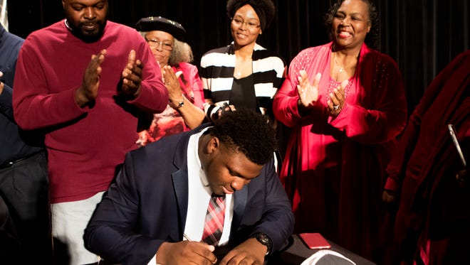 Neville defensive player Phidarian Mathis signs a contract to play for Alabama next year during National Signing Day at Neville High School in Monroe on Wednesday, February 1, 2017. His father Phil White, left, great-aunt Mary Marshall, second from left, aunt Kiki White, center, grandmother Trellis Brass, second from right, watch as his mother Tanya Mathis, far right, films with her iPhone.