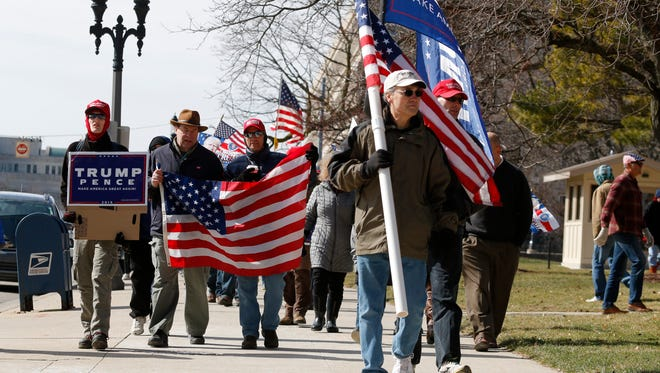 Trump supporters march around the state Capitol following a rally Saturday, March 4, 2017, in Lansing.