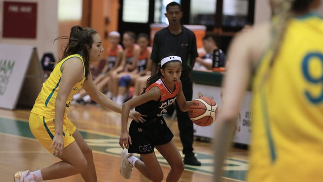 Team Guam's Alana Salas, a sophomore from George Washington High School, maneuvers between the trees of Australia in their semifinal game yesterday at the FIBA U17 Women's Oceania Championship at the UOG Calvo Field House. Australia beat Guam 154-12. Guam will face Samoa at noon Saturday for the bronze medal.