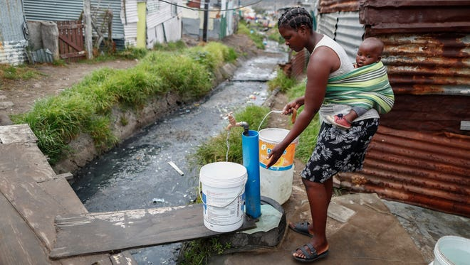A resident of Masiphumelele informal settlement collects drinking water from a communal municipal tap in Cape Town, South Africa, on Jan. 30, 2018.