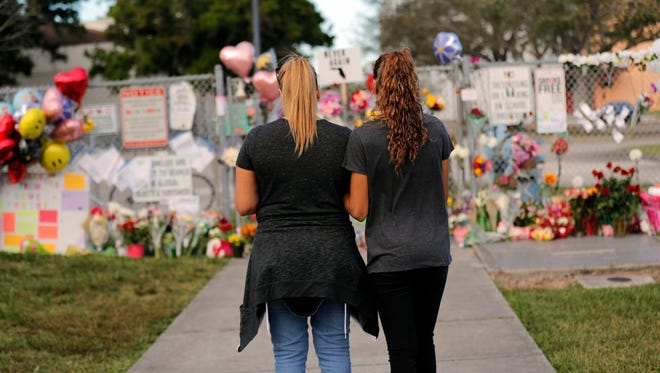 Sara Smith, left, and her daughter Karina Smith visit a makeshift memorial outside the Marjory Stoneman Douglas High School, where 17 students and faculty were killed in a mass shooting on Wednesday, in Parkland, Fla., Feb. 19, 2018. Nikolas Cruz, a former student, was charged with 17 counts of premeditated murder on Thursday.