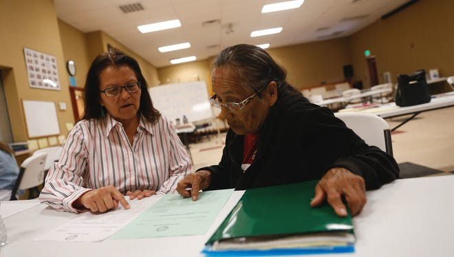 Julie Redhouse, left, translates for Rosie A. Chavez while looking over legal documents March 29 at the Upper Fruitland Chapter house as part of a free program that helps Native Americans put together a will.