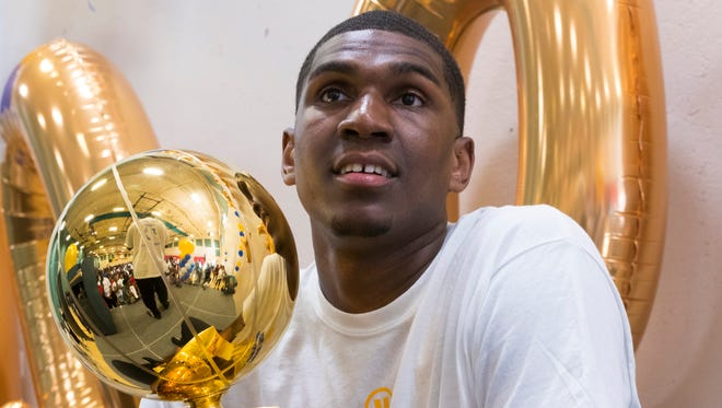 Kevon Looney holds this year's NBA Championship trophy that he helped win as a member of the Golden State Warriors. Looney was  at the Northside YMCA in Milwaukee on Friday and took part in the Running Rebels Pause 4 Peace celebration.