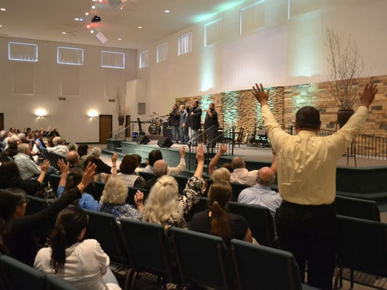 Attendees give praise as the Keepers of the Faith gospel