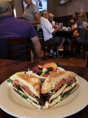 A portobello mushroom veggie sandwich is served with fresh fruit at Hollywood Beach Café.