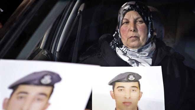 The mother of Jordanian pilot Lt. Muath al-Kaseasbeh holds a picture of her son, who is held by Islamic State militants, during a sit-in in front of the Cabinet offices in Amman, calling for his release.