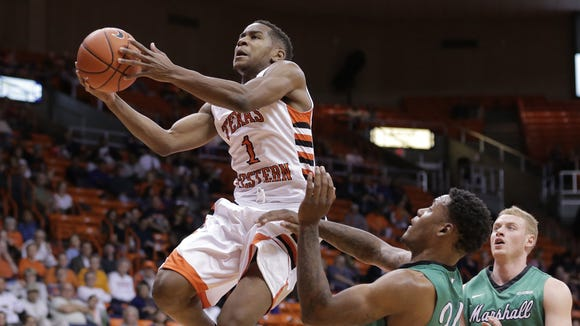 UTEP guard Dominic Artis sails past Marshall's James Kelly on his way to the hoop Thursday night at the Don Haskins Center. The Miners won, 112-108.
