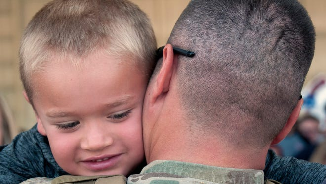 Sgt. 1st Class Kevin Vogt hugs his 6-year-old son Gavin during the unit's deployment return from Kuwait at Atlantic Aviation in Reno, July 6, 2017. The 485th Military Police Company, headquartered in Reno, performed customs operations from October 2016 until June in Kuwait and other Middle East countries. The 485th's return marks the end of a busy series of deployments for the Nevada Army Guard, which had about 460, or 15 percent, of its Soldiers deployed in autumn 2016.