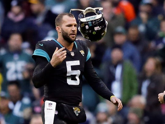 FILE- In this Oct. 28, 2018, file photo, Jacksonville Jaguars quarterback Blake Bortles (5) tosses his helmet after failing in a two-point conversion attempt during the second half of an NFL football game against the Philadelphia Eagles at Wembley stadium in London. When things go sour, an NFL team's fan base often points to two people: the guy calling plays on the sideline, and the man behind center trying to execute them.  (AP Photo/Tim Ireland, File)
