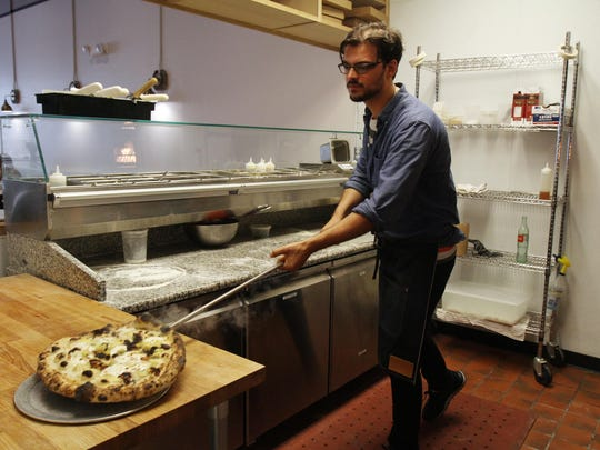 Steve Mignogna of Ocean Grove, co-owner of Talula's, prepares the Spring Spud sourdough pizza, made with new potatoes, bacon fat basamella, garlic, Benton's bacon, aged provolone and fresh herbs, inside his Cookman Avenue restaurant in Asbury Park.