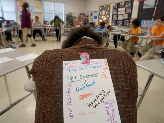 Students and teachers in Suzanna McMahon's eighth grade social studies class went around the room and wrote compliments to classmates on pieces of paper attached to their backs.