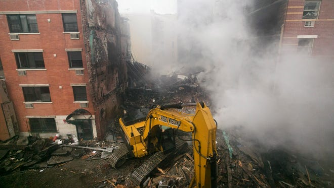 An excavator works to remove debris from  the site of a building explosion, Thursday, March 13, 2014 in New York. Rescuers working amid gusty winds, cold temperatures and billowing smoke pulled four additional bodies Thursday from the rubble of two New York City apartment buildings, raising the death toll to at least seven from a gas leak-triggered explosion that reduced the area to a pile of smashed bricks, splinters and mangled metal.  The explosion Wednesday morning in East Harlem injured more than 60 people.