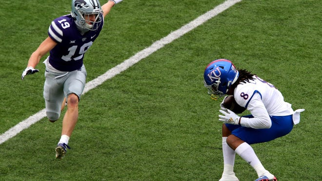 Kansas Jayhawks wide receiver Kwamie Lassiter II (8) looks for room to run against Kansas State Wildcats defensive back Ross Elder (19) during a game at Bill Snyder Family Football Stadium.