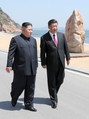 Chinese President Xi Jinping, right, walks with North Korean leader Kim Jong Un during a meeting in Dalian in northeastern China's Liaoning Province in May.