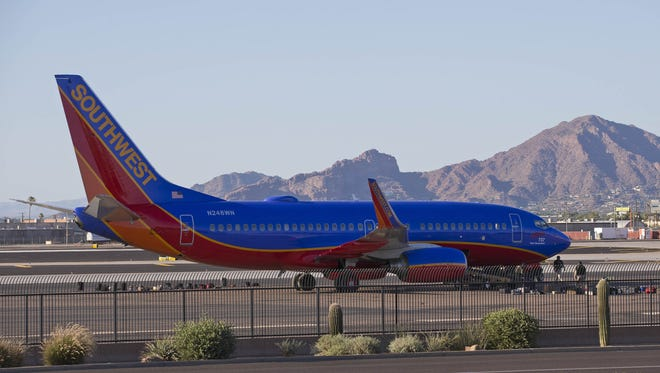 A Southwest Airlines plane is parked on the side of a runway at Phoenix Sky Harbor Airport.