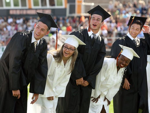 """The Somerville High School graduation takes place on the football field at the school. Students watch to see if the body """"wave"""" they started makes it all the way down the line of students waiting for graduation to begin, June 20, 2014. Somerville NJ. photo by Kathy Johnson  BRI 0621 Somerville Grad"""