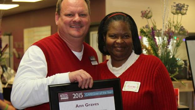 """Ann Graves receives her """"CAREGiver of the Year"""" award from Bryson McQuiston, owner of the Home Instead Senior Care Jackson office."""