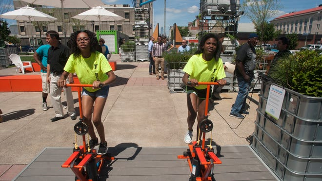 Brianna Pearson (left) and Asia Young, both 12, use a peddle pump to activate water jets and turn the fountain wheels at a pop-up park in Camden.