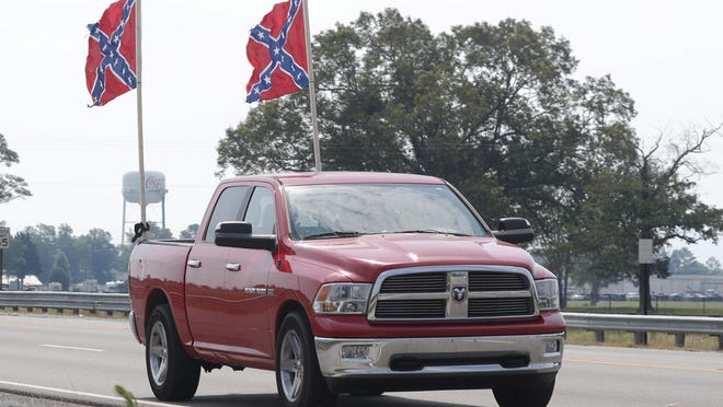 A truck flying Confederate flags passes by the Talladega Superspeedway prior to the NASCAR Cup Series race at the in Talladega Ala., on Sunday, June 21.