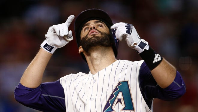 Arizona Diamondbacks' J.D. Martinez points and looks to the sky as he arrives at home plate after hitting a home run against the Colorado Rockies during the third inning of a baseball game Thursday, Sept. 14, 2017, in Phoenix. (AP Photo/Ross D. Franklin)