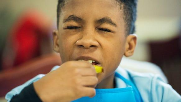 Zayne Rockamore, 10, tries a piece of starfruit for
