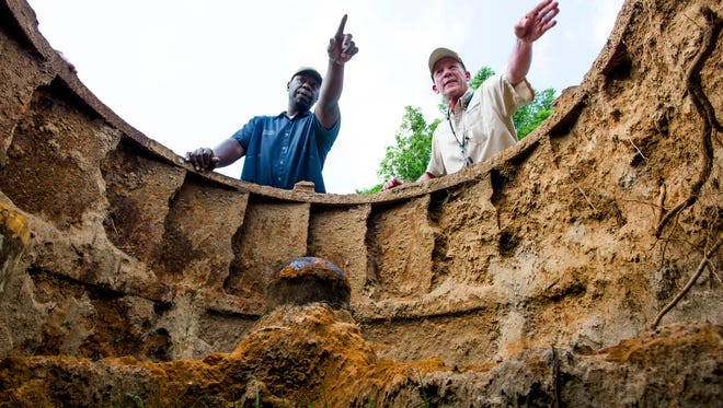 Kenya Battle, left, and Skip Lobmiller look at an old mill turbine, on Tuesday May 10, 2016, that they helped pull from Autauga Creek in Prattville, Ala.