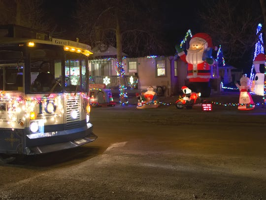 The Great Falls Historic Trolley drives by a home decorated