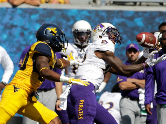 East Carolina wide receiver Trevon Brown (88) catches the ball on his way to a touchdown while being defended by West Virginia cornerback Corey Winfield (20) during the second half of an NCAA college football game, Saturday, Sept. 9, 2017, in Morgantown, W.Va. West Virginia defeated East Carolina 56-20. (AP Photo/Raymond Thompson)