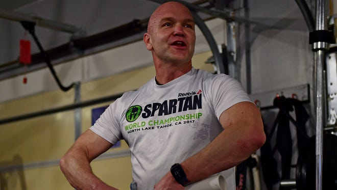 Andy Bell from Fairview Township lifts a weight during a Spartan Strong class at Run Higher Training in Lewisberry, Pa. on Tuesday, Feb. 20, 2018. Bell owns Run Higher Training, which is run out of a converted garage at his home. Bell, a teacher at Cedar Cliff high school, lost 100 pounds after starting his fitness journey with a 5K. Now, he's a Boston Marathon qualifier.