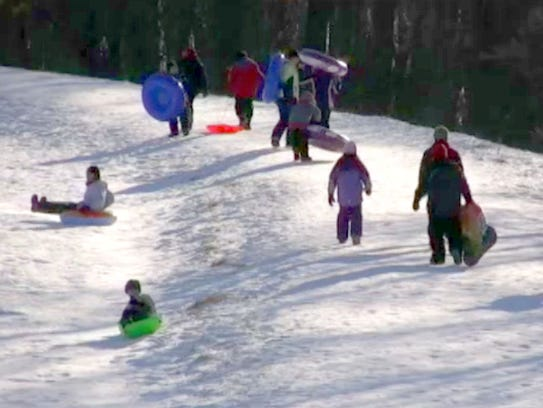 Sledders hike up the Mee-Kwon Park hill north of Mequon in 2010.