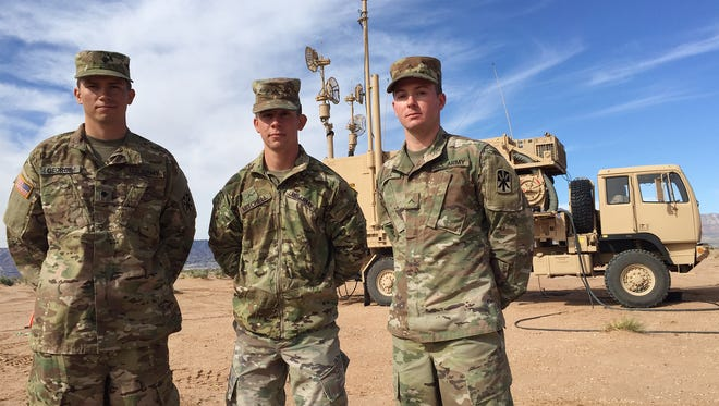 Soldiers from Beast Mode Battery, 2-43 ADA from are left, Spc. Paul George, Pvt. Brandon Mitchell and Pvt. Tyler Kissel. They are standing in front of a Patriot engagement control station.