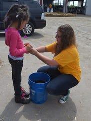 Waupun FFA President, Mykayla Kuhn helps an elementary